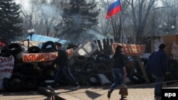 People walk past a barricade near the Ukrainian Security Service building in Luhansk occupied by pro-Russian activists on April 15.