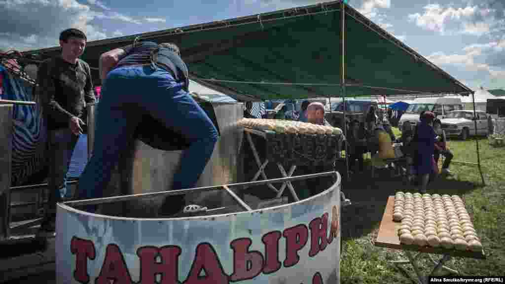 Чоловіки готуються випікати коржі в тандирній печі