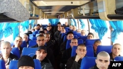 Afghan prisoners sit in a bus in Konduz on February 4, when Afghanistan and Tajikistan exchanged prisoners for the first time.