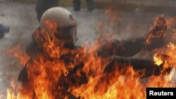 A riot policeman falls after being hit with a Molotov cocktail in Athens.