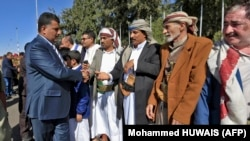 Yemen -- A member of the Huthi delegation (L) returning from peace talks in Sweden shake hands with supporters upon arrival at Sanaa International Airport in the Yemeni capital on December 14, 2019. - The Huthi rebel delegation returned on December 14 to