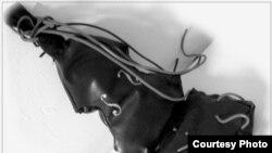 Инсталляция CelloClaus - имитация футляра виолончели из искусственной кожи, переходящего в эрзац-портфель с порванными «струнами-проводами-артериями»