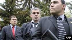 Georgian President Mikheil Saakashvili (left) is surrounded by bodyguards as he visits the Mukhrovani military base after a reported mutiny by soldiers.