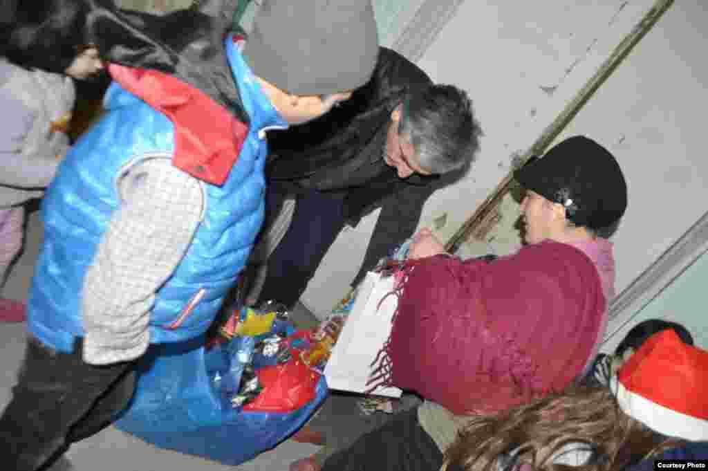 Volunteer Santas bring in bags of gifts.