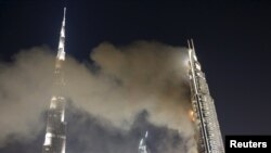 UAE - The Address Downtown Dubai hotel and residential block (R) is seen engulfed by fire as the Burj Khalifa, the tallest building in the world, is seen on the left, during the New Year celebrations in Dubai January 1, 2016