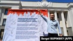 Святослав Вакарчук у здания Верховной рады Украины со списком обязательств депутатов его партии