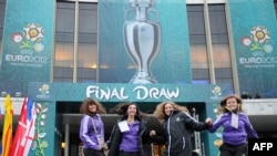 UEFA volunteers jump in front of the National Palace of Arts in Kyiv ahead of the December 2 draw.