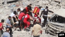 Syrian rescue workers carry a victim on a stretcher following a reported air strike on the rebel-held northwestern city of Idlib on August 17.