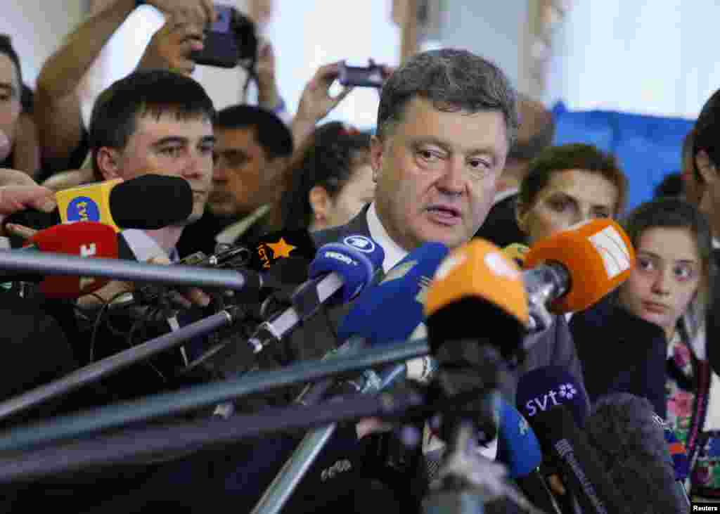 Ukrainian businessman and presidential candidate Petro Poroshenko (center) speaks to journalists after casting his vote in Kyiv.