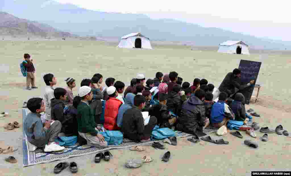 Afghan refugees, who have voluntarily returned from neighboring Pakistan with assistance from the United Nations High Commissioner for Refugees (UNHCR), attend an open-air school outside their temporary shelters in Laghman Province. (epa/Ghulamullah Habibi)