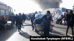 «Құлагер» базарындағы өрт кезінде жүктерін алып бара жатқан азаматтар. Алматы, 17 қараша 2013 жыл.