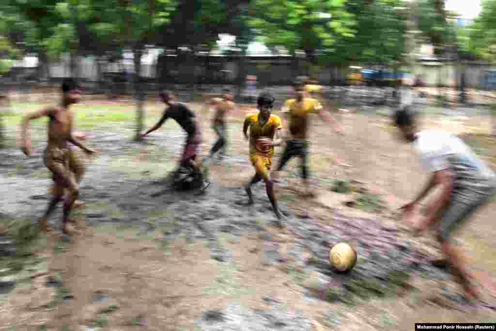 Boys play football on the muddy ground of a park on a rainy day in Dhaka, Bangladesh. (Reuters/Mohammad Ponir Hossain)