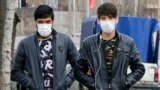 Iranians wearing face masks walk on a street of Tehran, February 24, 2020.