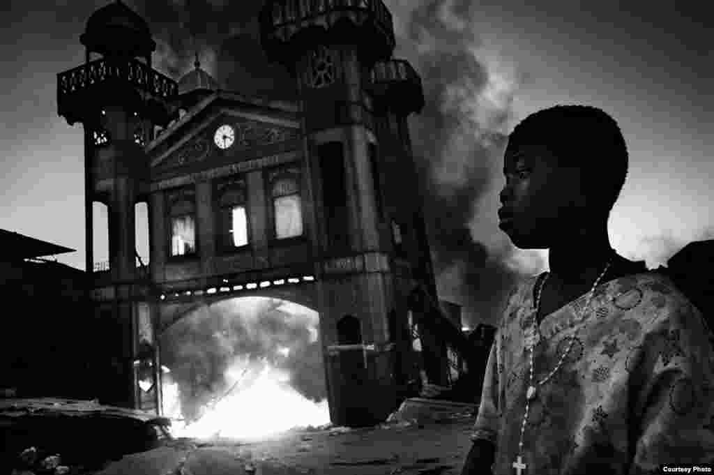 1-е место / События / одиночные фотографии Рикардо Вентури, Италия, Contrasto Девочка смотрит, как горит старый Железный Рынок, Порт-о-Пренс, Гаити, 18 января 2010.