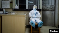A medical worker in a protective suit takes a break during her night shift at a community health service center in Wuhan.