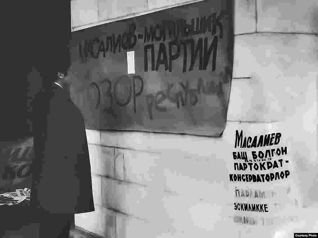 """Кыргызстандын коммунисттик бийлигине каршы саясий ачкачылык. Фрунзе (Бишкек) ш., 22-28.10.1990. - Кыргызстандагы коммунисттик режимге каршы """"КДК"""" уюштурган саясий ачкачылык маалындагы Кыргызстан Компартиясынын ошондогу лидери Абсамат Масалиевге каршы плакаттардын айрымдарын борбор шаардын тургуну окуп жатат. Бул сыяктуу плакаттар """"Ак Үйдүн"""" керегесине жана борбор шаардын ар кыл булуң-бурчуна илинген. 1990-жылдын 23-октябры. """"Майдан"""" эркин гезитинин архивинен."""