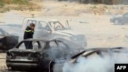 Человек стоит на месте взрыва заминированного автомобиля. Иллюстративное фото