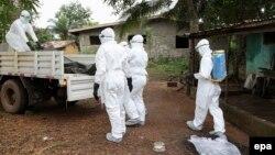 Լիբերիա - Բուժաշխատողները տեղափոխում են էբոլայից մահացածի դին, օգոստոս, 2014թ․