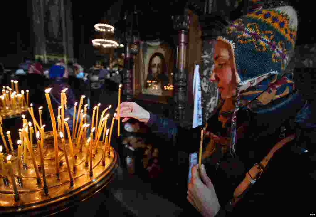 A woman lights a candle during the Orthodox Christmas Eve mass at St. Volodymir Cathedral, in the Ukrainian capital, Kyiv.