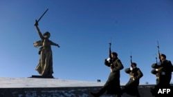 Honor guards march past the giant monument built to honor those who died in the World War II Battle of Stalingrad.