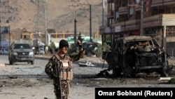 A member of the Afghan security forces keeps watch at the site of a suicide blast in Kabul on November 13.