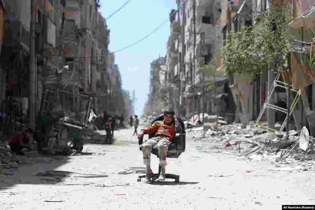 A boy sits in a chair along a damaged street at the city of Douma near Damascus, Syria. (Reuters/Ali Hashisho)