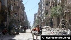 Дума шаарынын чок ортосунда отурган бала. Сирия, 16-апрель, 2018-жыл.