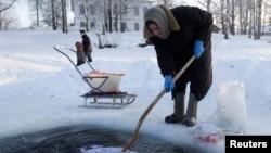Старушка полощет белье в проруби на Сиверском озере в городке Кириллов
