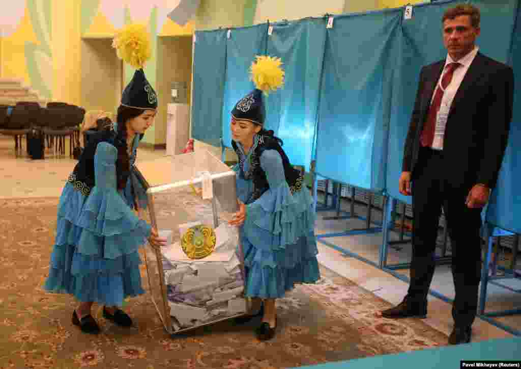 Members of a local Kazakh election committee carry a ballot box before counting votes during the presidential election in Almaty on June 9. (Reuters/Pavel Mikheyev)