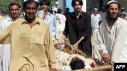 Local residents carry an injured pro-government elder to a hospital after an ambush in Bannu, Pakistan on September 24.