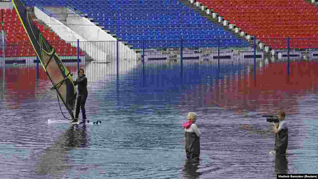A man windsurfs at flooded Lenin Stadium, the home arena of the local soccer club SKA-Energia, in the Russian Far East city of Khabarovsk. (Reuters/Vladimir Barsukov)