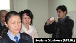 Экс-председателя агентства по статистике Анар Мешимбаеву (в центре) ведут в зал суда. Астана, 27 января 2014 года.