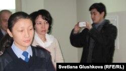Экс-председателя агентства по статистике Анар Мешимбаеву (в центре) ведут в зал судебных заседаний. Астана, 27 января 2014 года.