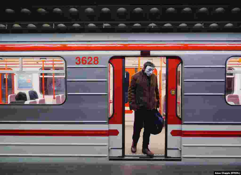Мужчина в маске Гая Фокса на выходе из вагона метро. Накануне мэр Праги написал в Тwitter'е, что жители должны закрывать рот и нос в транспорте: «Неважно, будут ли медицинские маски, маски собственного изготовления или шарф, это лучше, чем ничего».