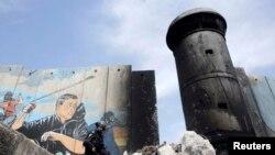 Израильская полицейская возле поврежденного участка заградительной стены вокруг лагеря палестинских беженцев Аида в Вифлееме