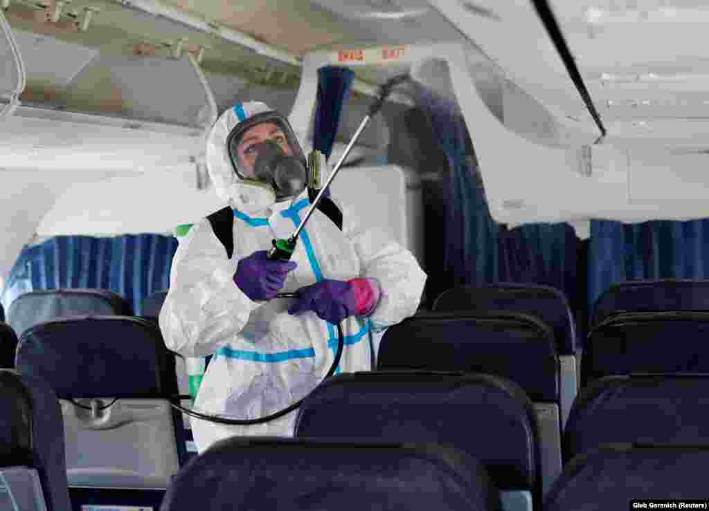 A worker sprays disinfectant inside a plane at Kyiv's Boryspil International Airport on June 13, after passenger flights out of the Ukrainian capital resumed.