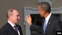 АҚШ президенті Барак Обама (оң жақта) Ресей президенті Владимир Путин жаққа қолын көтеріп тұр. Ресей, Санкт-Петербург, G20 саммиті, 5 қыркүйек 2013 жыл. (Көрнекі сурет)