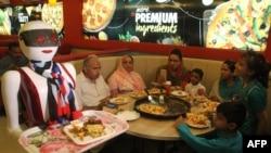 Робот-официант разносит заказы в пакистанской пиццерии. Мултан, 6 июля 2017 года