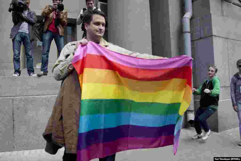 """Гей-активист разворачивает радужный флаг, сзаду уже набегает """"противник"""" гей-парадов."""