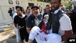 Триполиде жараланған адамды шерушілер көтеріп келеді. 15 қараша 2013 жыл.