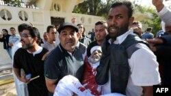 Шеру кезінде оқ тиіп жараланған адамды көтеріп келе жатқандар. Триполи, Ливия, 15 қараша 2013 жыл.