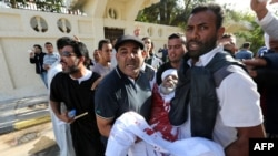 Мужчины несут раненого во время столкновений в Триполи. 16 ноября 2013 года.
