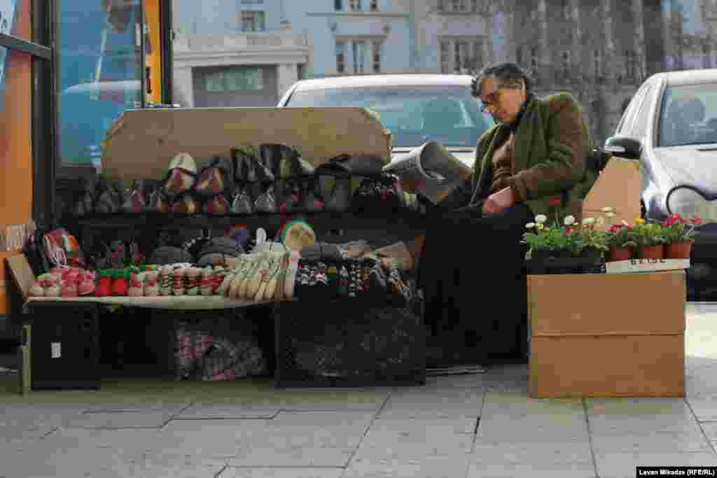 Hedging your bets: A street seller in Tbilisi offers winter clothing alongside spring flowers. Photo by Levan Mikadze.