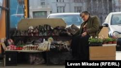 Təklifin sığortalanması: Tbilisidə küçə satıcısı yaz gülləri ilə yanaşı, qış geyimləri təklif edir. Levan Mikadze-nin fotosu
