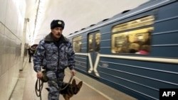 A police officer with a bomb-sniffing dog patrols the Lubyanka subway station in Moscow.