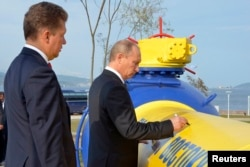 Then Prime Minister Vladimir Putin (right) and Gazprom CEO Aleksei Miller attend a gas-pipeline opening ceremony in the far eastern city of Vladivostok in 2011.