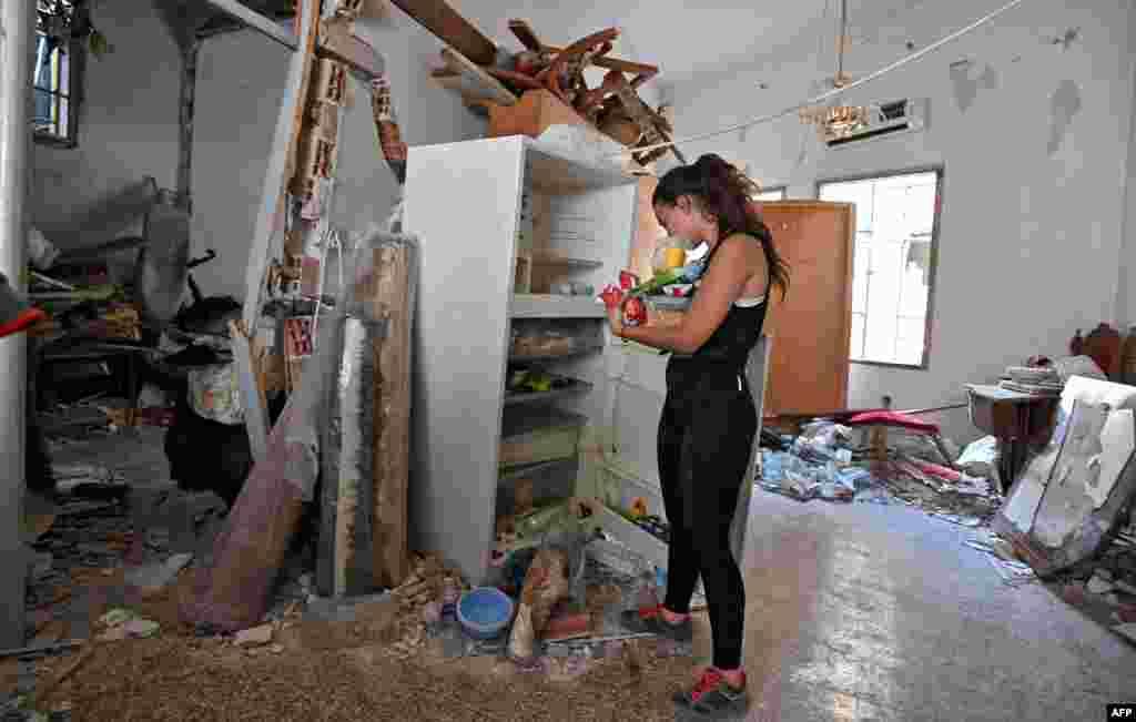 Жена го чисти домот разурнат од силната експлозија.