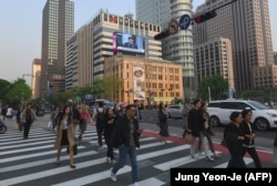 Люди переходят улицу в Сеуле. Иллюстративное фото.