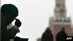 Нищенка, просящая подаяния, крестится на купола Кремля