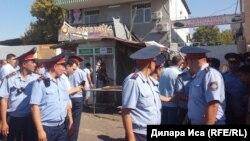 Шымкенттегі Орталық Қырғы базары алдындағы дүргіршектерді бұзып жатқан жерде жүрген полицейлер. 30 шілде 2018 жыл.